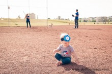 baby girl on a baseball field while mom and dad play ball