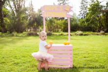 baby girl poses with her lemonade stand