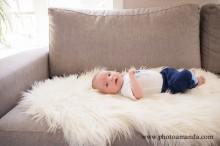 8 week old baby boy laying on sofa