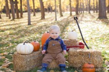 baby boy with some pumpkins and hay