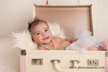 baby girl laying in a vintage suitcase