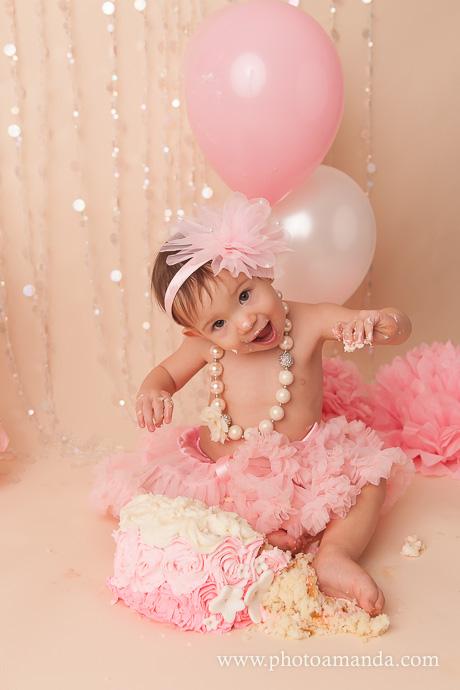 little girl having fun smashing her pink cake