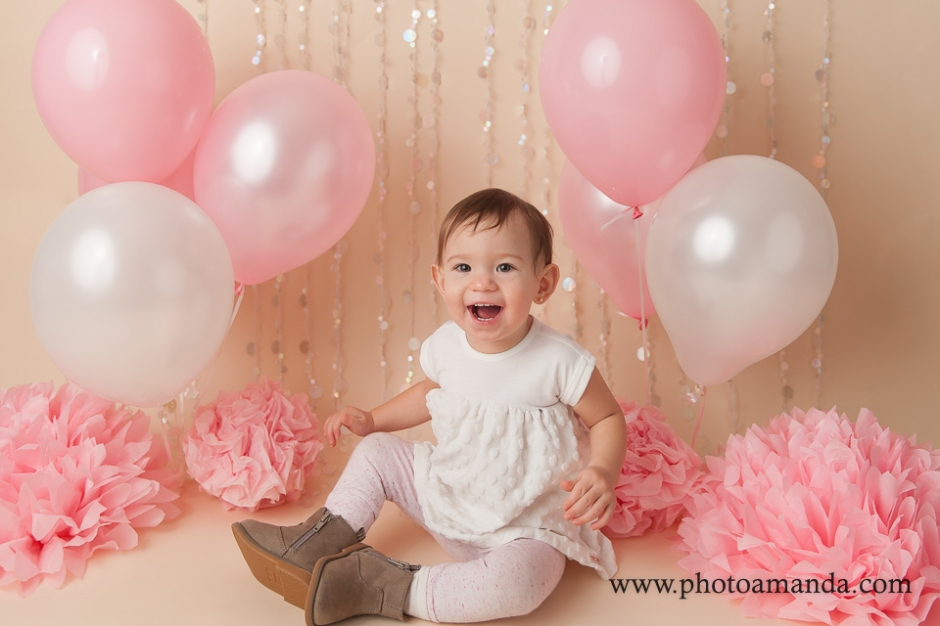 1 year old sitting with pink and white balloons