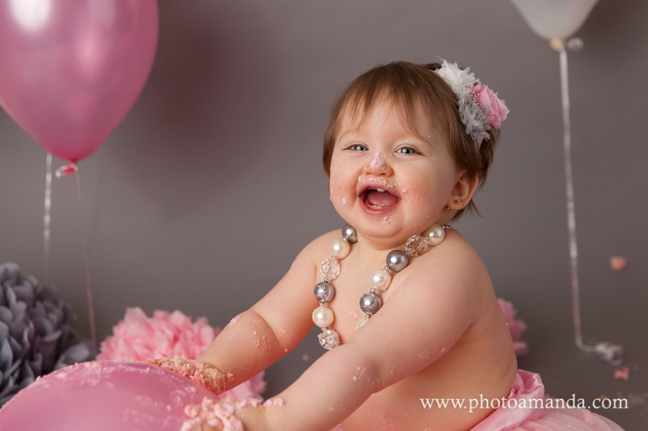 1yr old baby girl smashing her pink cake and looking at the camera smiling