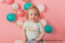 baby girl sitting on white bench in front of pink background with balloons