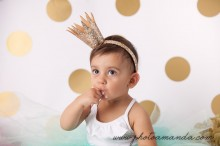 adorable baby girl eating cake with gold crown