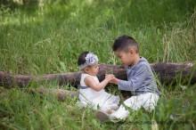 big brother showing littler sister a flower