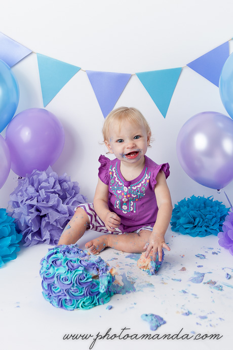 baby girl smiles while eating blue and purple cake